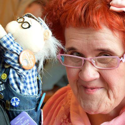 Punahiuksinen nainen poseeraa nuken kanssa lähikuvassa
