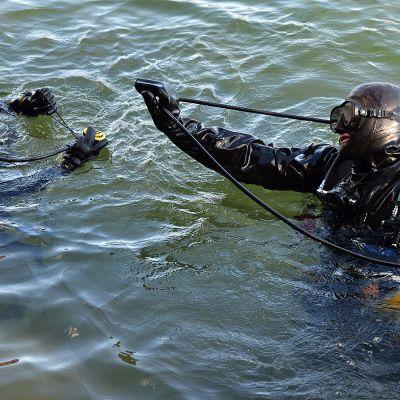 Nuori poika ja mies järvessä lähdössä sukeltamaan