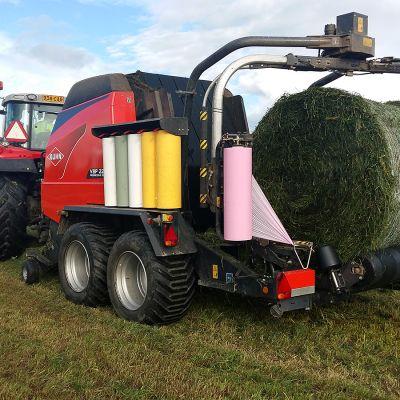 Traktorin vetämä paalain rehupaalilastissa