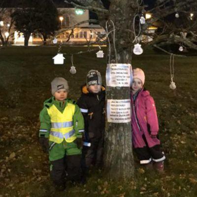 Barn runt ett träd som har reflexer hängandes från grenarna. Trädet är på en gräsmatta och barnen är klädda i vinterkläder. Det är mörkt ute.