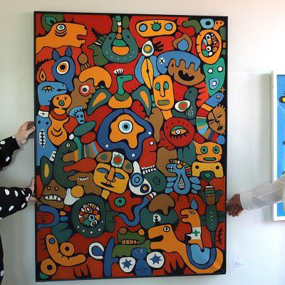 Nainen ja mies katsovat seinällä olevaa taulua