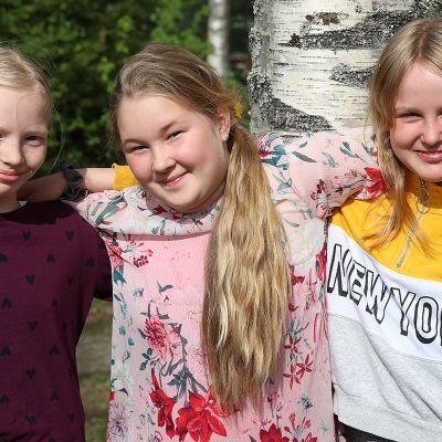 Kolme neljäsluokkalaista tyttöä yhteiskuvassa