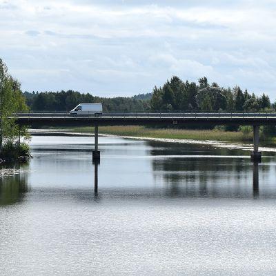 Järven yli kulkeva silta sivusta kuvattuna, sillalla kulkee pakettiauto