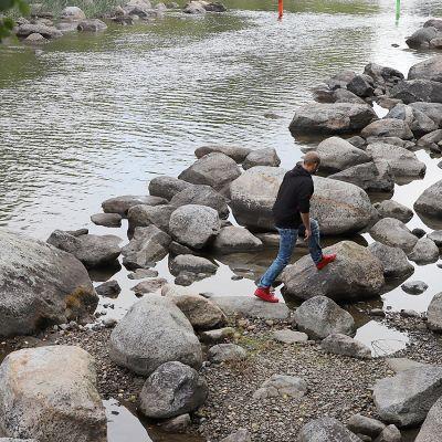 Mies loikkii vedenvähyydestä kärsivän virran kuivilla kivillä