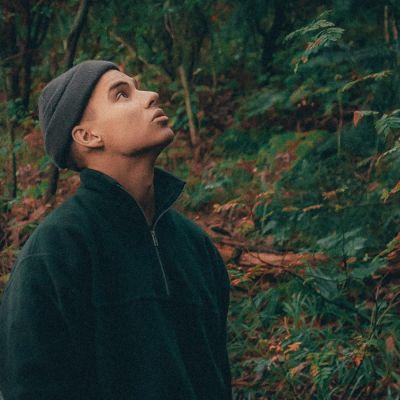 Pipopäinen mies seisoo metsässä ja katsoo yläviistoon.