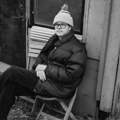 Manner istuu mustavalkoisessa kuvassa toppatakissa.