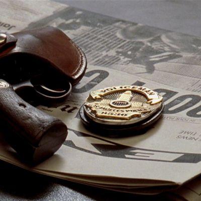 Revolveri koteloineen ja Los Angelesin poliisin virkamerkki makaavat pöydällä sanomalehden päällä. Kuva elokuvasta L.A. Confidential.