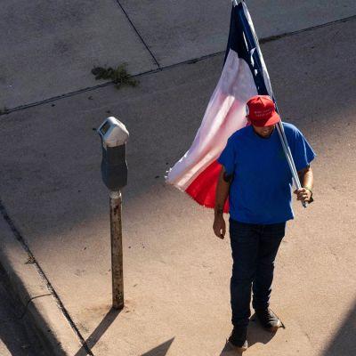 Kuvassa on mies, lippu ja miehestä jäävä varjo.