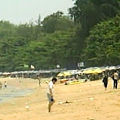 Ihmisiä rannalla Phuketissa Thaimaassa, uutisista 26.12.2004