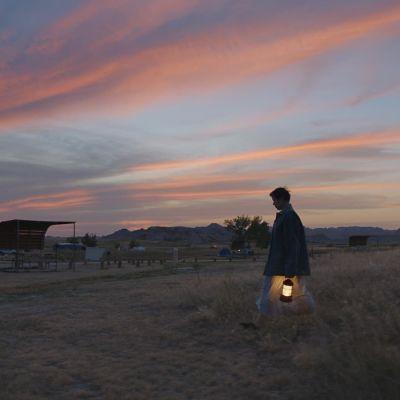 Fran i solnedgången med en lykta i handen.