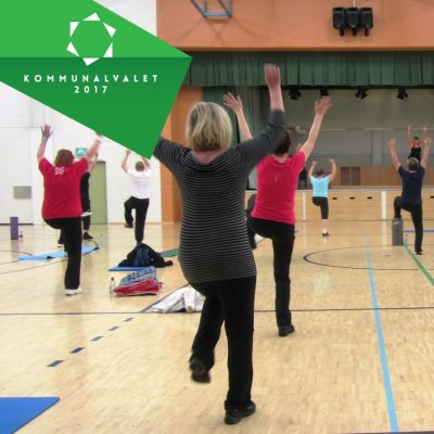 Pensionärer motionerar i en gymnastiksal.