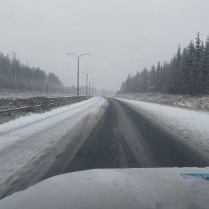 Auto ajaa lumisella tiellä räntäsateessa.