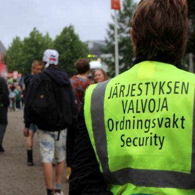 Järjestyksenvalvoja tarkkailee festivaaliväkeä Ilosaarirockissa.