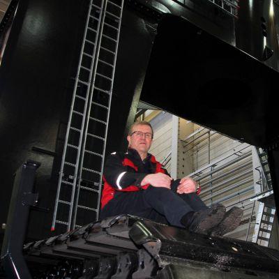 Valmisteilla oleva hydraulinen nosturi ja toimitusjohtaja Martti Toivanen.
