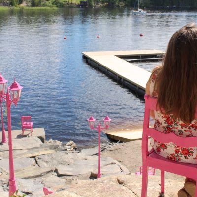 Vaaleanpunaisia talonpoikaistuoleja ja lyhtyjä rantakalliolla