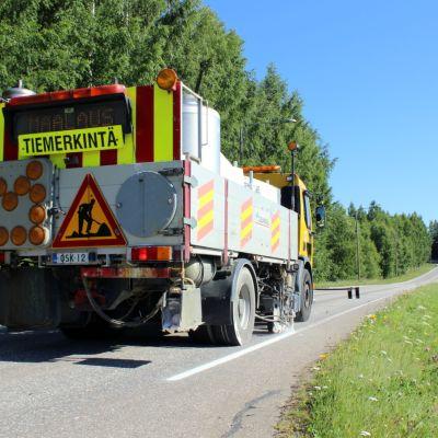 Tiemerkintäauto merkitsee maantien reunaviivaa. Auton perässä on huomiokylttejä.