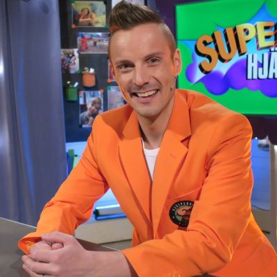 Programledaren Jontti granbacka sitter vid ett skrivborde i tv-studion tillsammans med tv-musen Plåstret