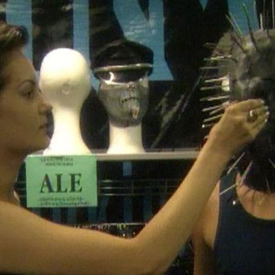Nainen ja mies sovittavat naamiota kaupassa