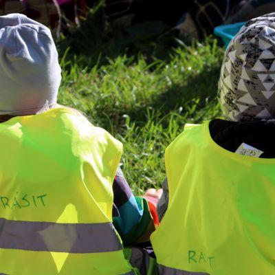 Kaksi lasta istuu nurmikolla huomioliivit yllään.