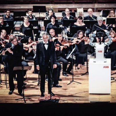 Orkesterin edessä valkoinen robotti, jonka kädessä tahtipuikko.