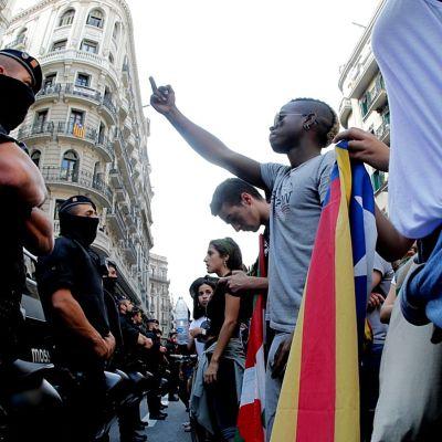 Mielenosoittaja näyttää poliisille keskisormea