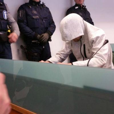 Gärningsmannen sitter med huva på i rättssalen.