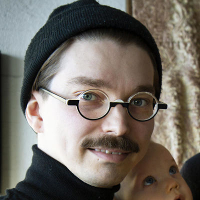 Kaksi silmalasipäistä miestä ja vauva.