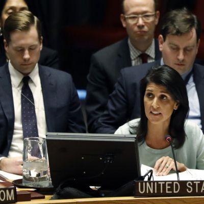 Tummahiuksinen nainen mintunvärisessä paidassa mikrofonin ja tietokoneruudun edessä, takana istuu miehiä puvut päällä.