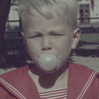 Pikkupoika kotkassa jauhaa purkkaa 1960-luvun alussa