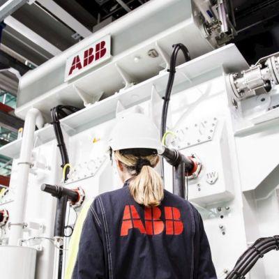 ABB-anställd i fabriken står framför en maskin.