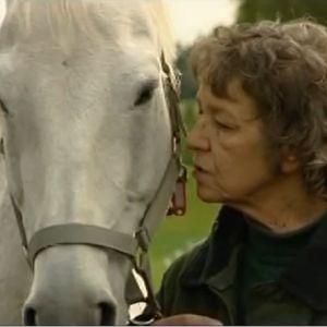 Sirkka Turkka valkoisen hevosen kanssa vehreällä taustalla.