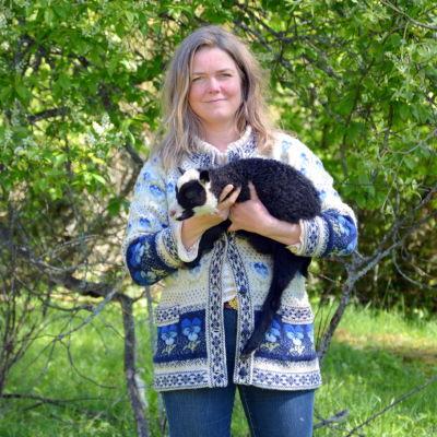 Anette Norrgrann utomhus med lammunge i famnen