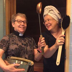 Rekolan kirkon pastori Vappu Olsbo (vas.) sekä kanttori Sirkku-Liisa Niemi saunan ovella löylykauha ja pesuharja käsissään.