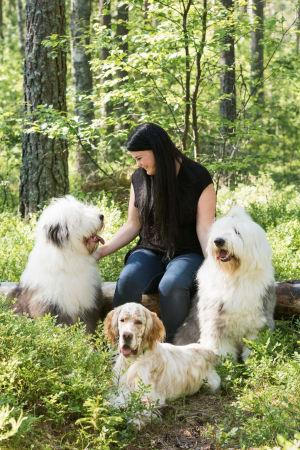 Hundtränare Anna Sydänheimo i en skogsglänta med sina tre hundar.