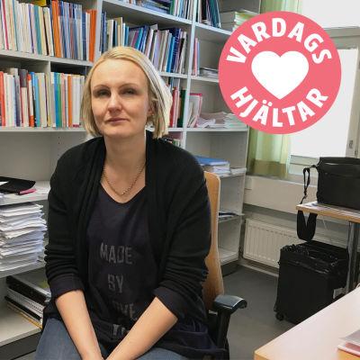 Linnéa Henriksson sitter på en stol framför en bokhylla full med böcker.