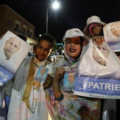 Valkoisiin pukeutuneita Mohamed ould Ghazouanin kannattajia julisteiden kanssa