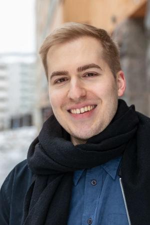 Hermanni Hyyryläinen seisoo hymyilevänä ulkona kadulla kerrostalon edessä.