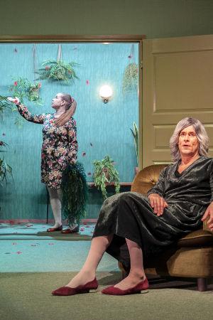Etualalla Tommi Korpelan näyttelemä nainen istuu nojatuolissa vakavana. Taustalla oviaukossa Katja Küttnerin naishamo ruusjen keskellä.
