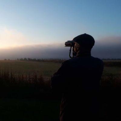 Man står med ryggen mot kameran och med kikare spanar han ut på en åker. I soluppgången.