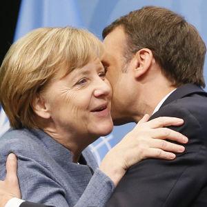Emanuel Macron och Angela Merkel kindpussas i Bonn.