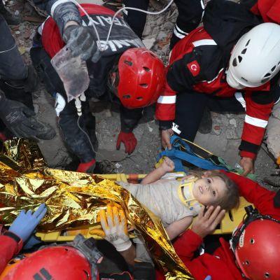 Turkin hätätilaviranomaisten julkistama kuva pelastajista, jotka kantavat nelivuotiasta Ayda Gezginiä turvaan maanjäristyksessä romahtaneen talon raunioista Bayraklin alueella Izmirissä.