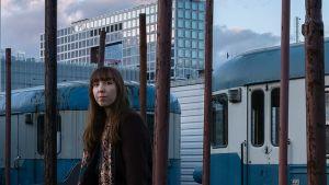 Artisten Nightbird sitter på en tågvagn, ser in i kameran, i bakgrunden skymning och glashus.