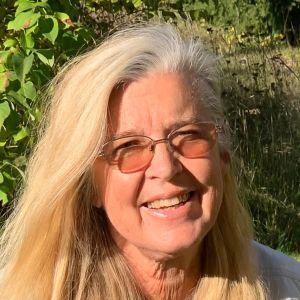 En kvinna med blont hår och glasögon brevid en man med keps på huvudet.