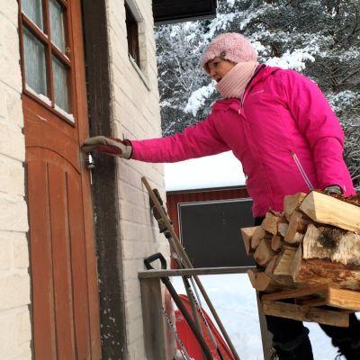 Pakkasilla kodinhoitaja Arja Heikkinen kantaa puut asiakkaalle  Nurmeksen Puiroossa.