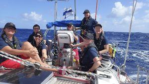 Sju kvinnor ombord på en segelbåt ute på öppet hav. Soligt. Ser varmt ut. Kvinnorna klädda i t-skjortor.