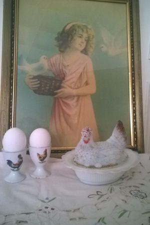En tavla i bakgrunden föreställande en flicka med två vita duvor. I förgrunden två äggkoppar och en vit porslinshöna.