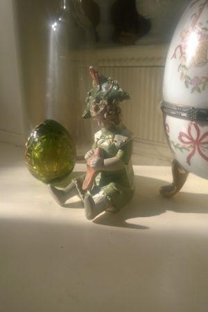 Ett grönt glasägg och en porslinsfigurin.