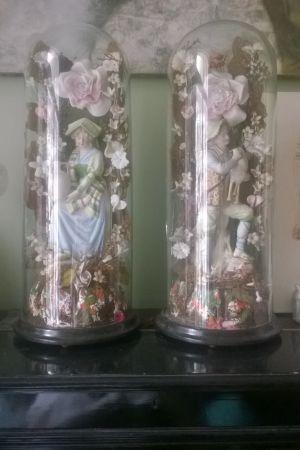 Två glasklockor från 1800-talet med skulpturer i.