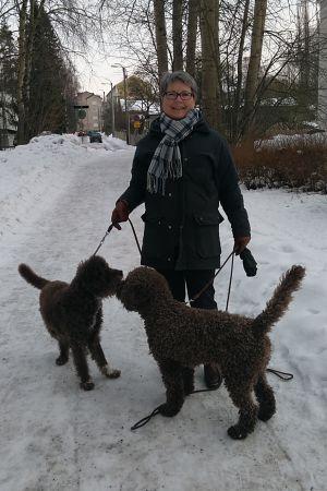 En kvinna med två hundar i koppel.