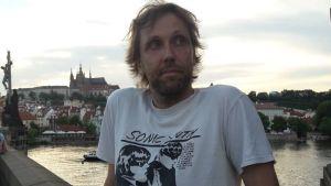 Man står på Karlsbron i Prag, skymning, floden syns och slott i bakgrunden